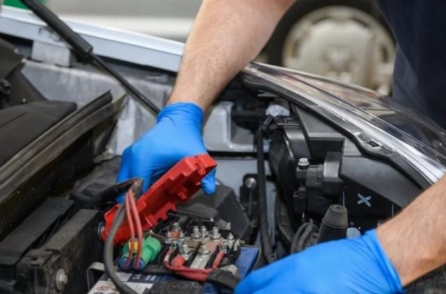 taller-coche-bateria-mecanico-trabajo